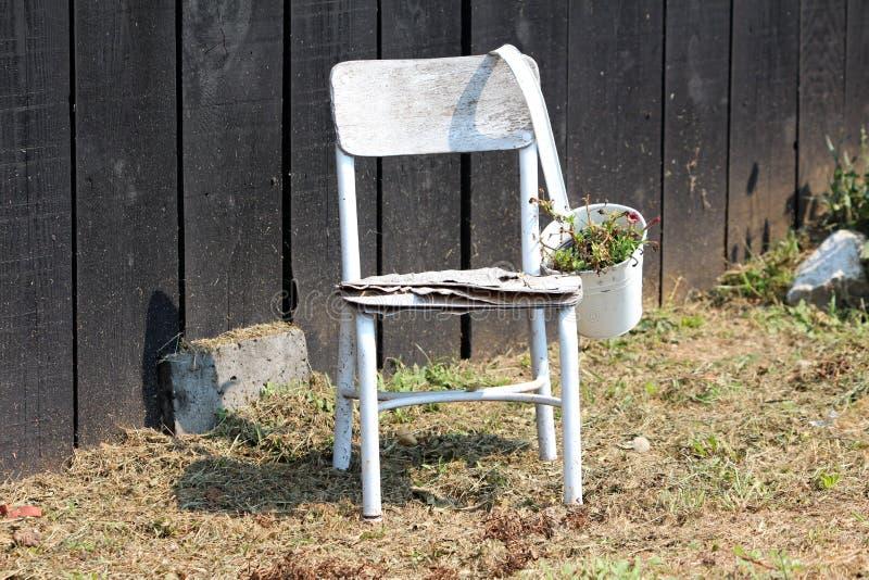 Silla dilapidada vieja blanca de madera con la maceta del metal usada como decoración del patio trasero delante de la pared de ma foto de archivo libre de regalías