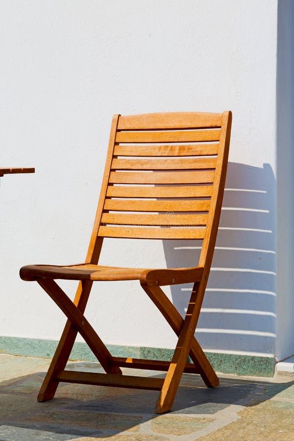 silla en la isla de Grecia del banco viejo de los paros cerca de un antiq del ladrillo imagenes de archivo