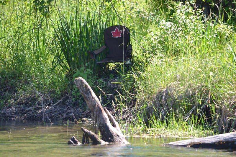 Silla en la orilla del río, hoja de arce fotos de archivo
