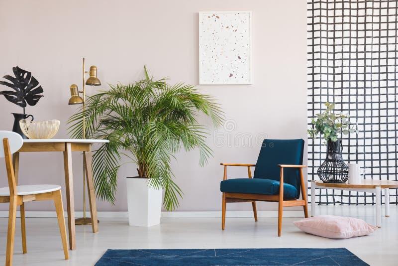 Silla en la tabla de madera en el comedor brillante interior con las plantas y el cartel sobre la butaca Foto verdadera stock de ilustración