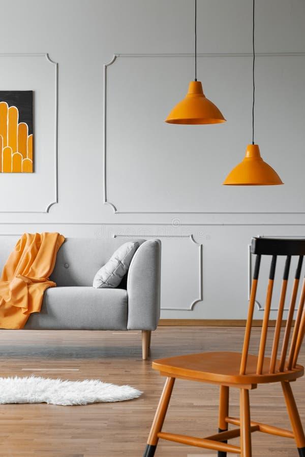 Silla en un interior de la sala de estar con un moldeado de la pared, una l?mpara anaranjada y un sof? Foto verdadera fotografía de archivo