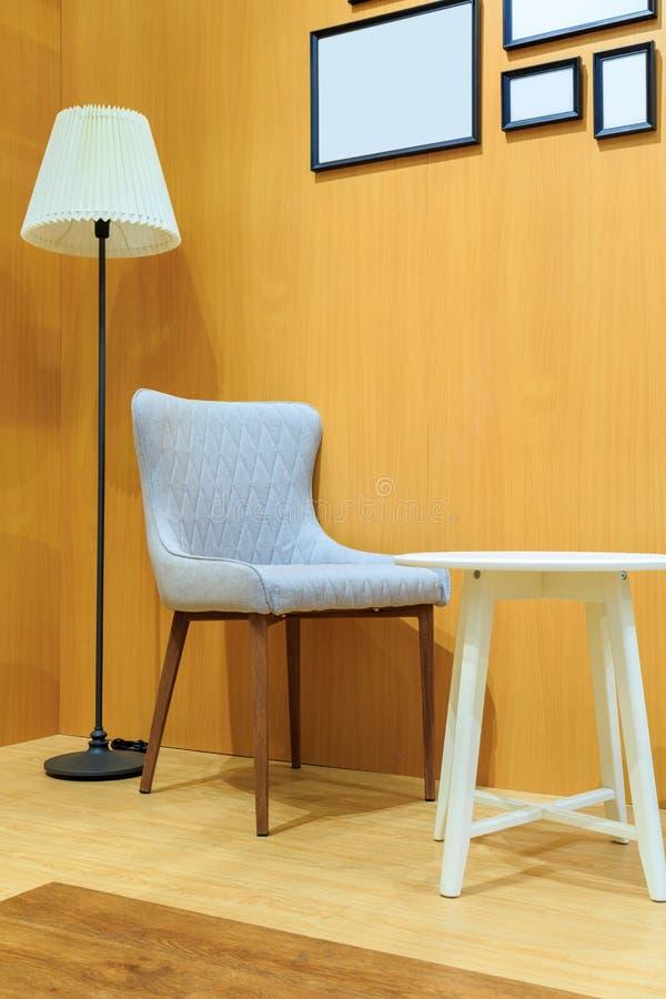 Silla gris del amortiguador y silla de madera blanca con la lámpara en el livi de madera fotos de archivo libres de regalías