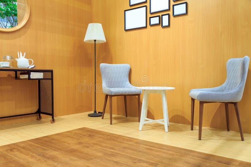 Silla gris del amortiguador y silla de madera blanca con la lámpara en li de madera foto de archivo libre de regalías