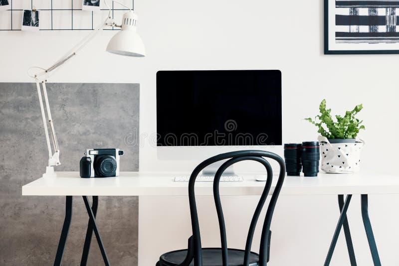 Silla negra por un escritorio blanco con un ordenador y una lámpara en un interior moderno de Ministerio del Interior para un fre foto de archivo