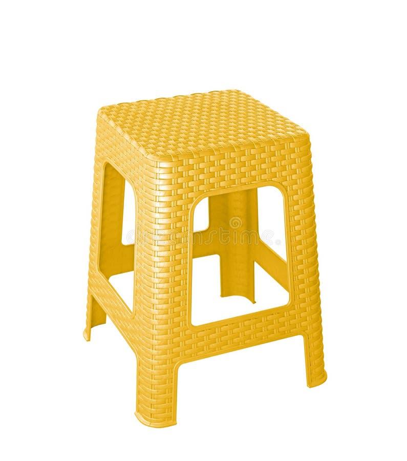 Silla plástica amarilla aislada en el bsckground blanco imagenes de archivo