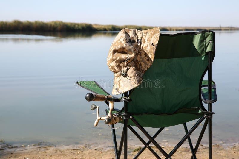 Silla que acampa con la caña de pescar en la orilla foto de archivo