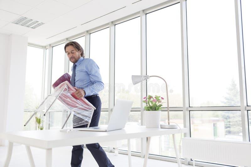 Silla que lleva del hombre de negocios maduro envuelta de plástico en la nueva oficina imagenes de archivo
