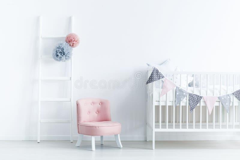 Silla rosada al lado de la cuna blanca en interio en colores pastel del dormitorio del ` s del bebé foto de archivo libre de regalías