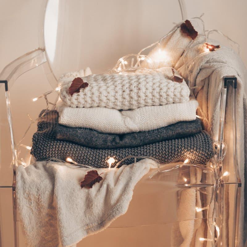 Silla transparente plástica - suéteres calientes Pila de ropa hecha punto en fondo caliente, suéteres, géneros de punto, concepto fotografía de archivo