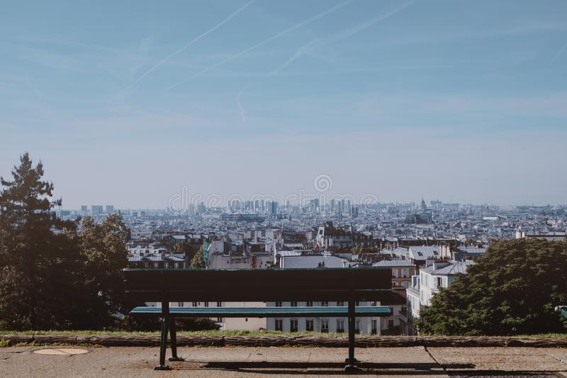 Silla vac?a del banco de madera en jard?n en la estaci?n de verano con la ciudad grande en Francia fotos de archivo