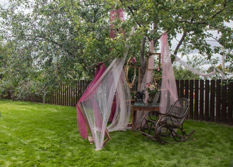 Silla vieja del vintage con los marcos y las flores románticos en hierba verde fotos de archivo
