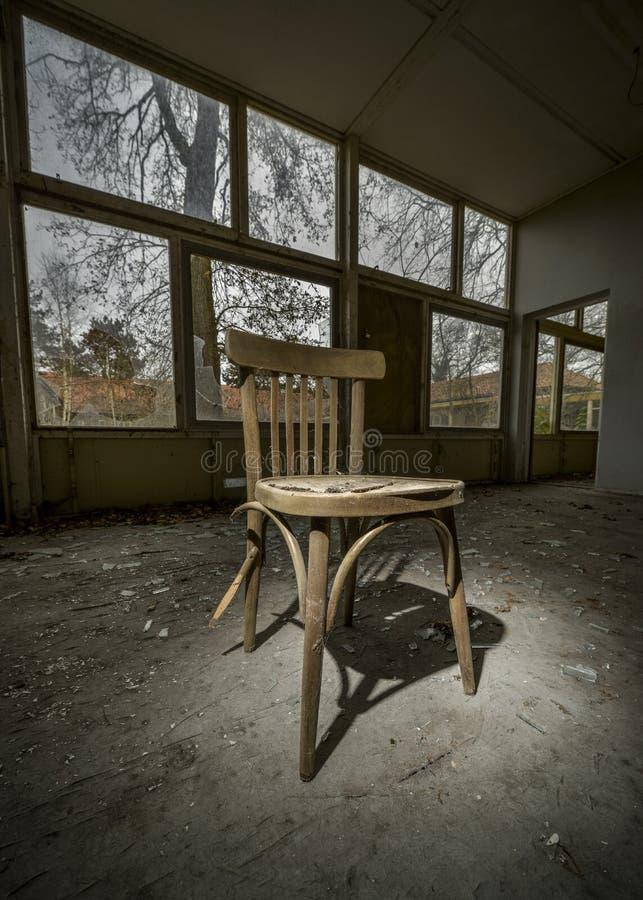 silla vieja en el edificio arruinado imagenes de archivo