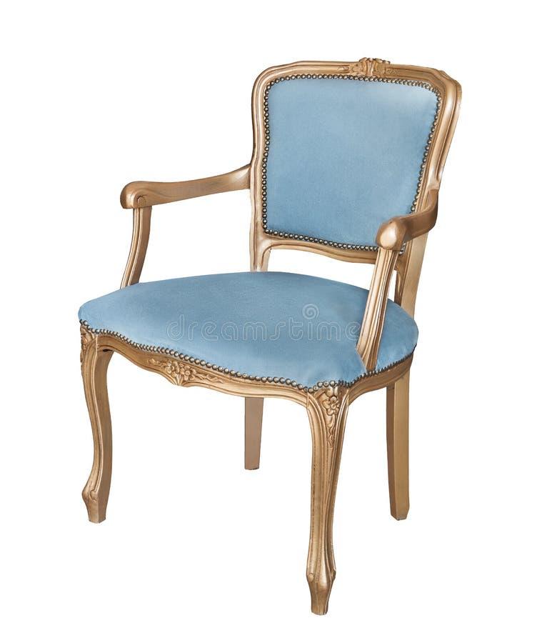 Silla vieja magnífica con las piernas del oro y apoyabrazos y acolchado azul del velor aislados en el fondo blanco Estilo retro M fotos de archivo