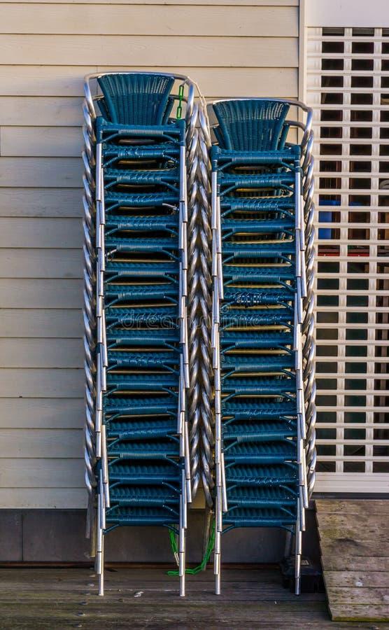 Sillas apiladas al lado de una persiana enrrollable cerrada, hora de límite en la industria de la restauración imagen de archivo