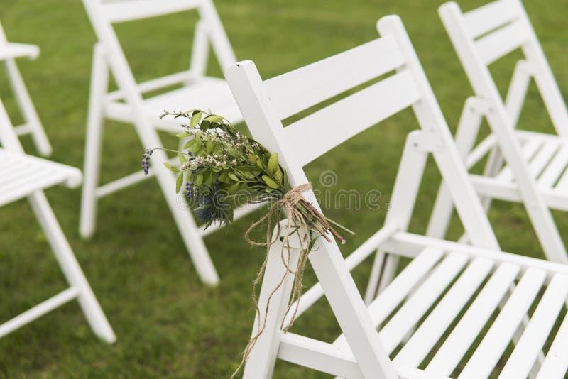 Sillas blancas de la boda adornadas con las flores frescas en una hierba verde Vacie las sillas de madera para las huéspedes en c fotos de archivo