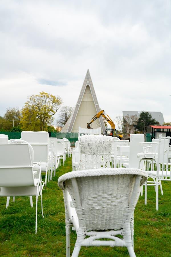185 sillas blancas vacías de conmemoración con símbolos del cambio en máquina del movimiento de tierras y catedral anglicana tran fotos de archivo