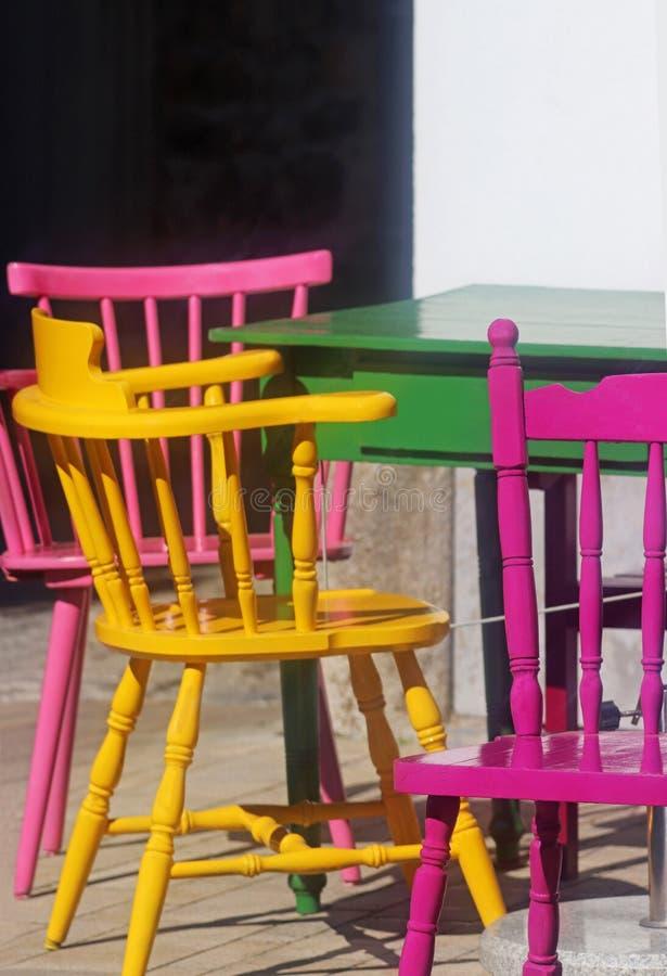 Sillas coloreadas multi y una tabla en una acera imagen de archivo