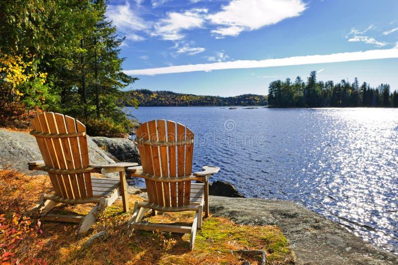 Sillas de Adirondack en la orilla del lago imagenes de archivo