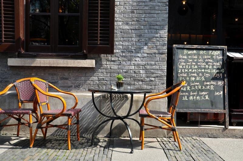 Sillas de bastón de la tabla del restaurante y menú al aire libre de la pizarra imágenes de archivo libres de regalías