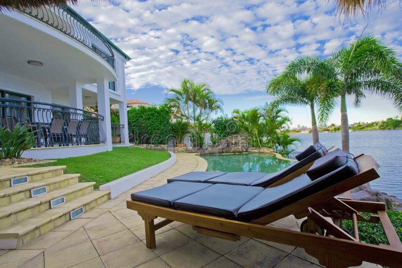 Sillas de cubierta por la piscina en la mansión de la línea de costa fotos de archivo libres de regalías