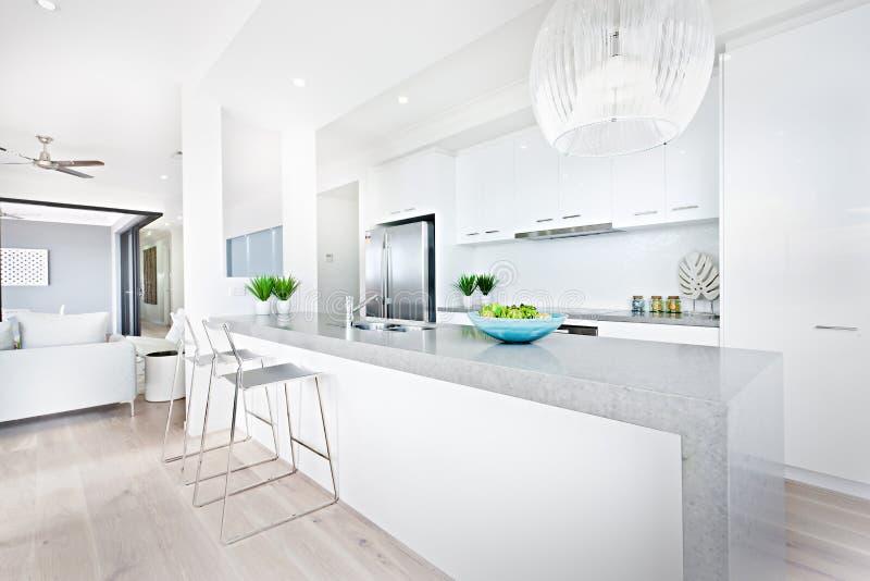 Sillas de la cocina y luces de lujo de la ejecución con las paredes blancas imagen de archivo