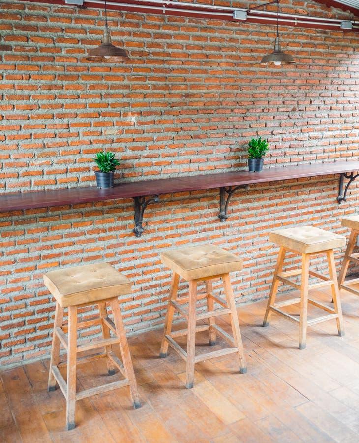 Sillas de madera con el asiento de cuero contra la pared de ladrillo roja en café fotos de archivo