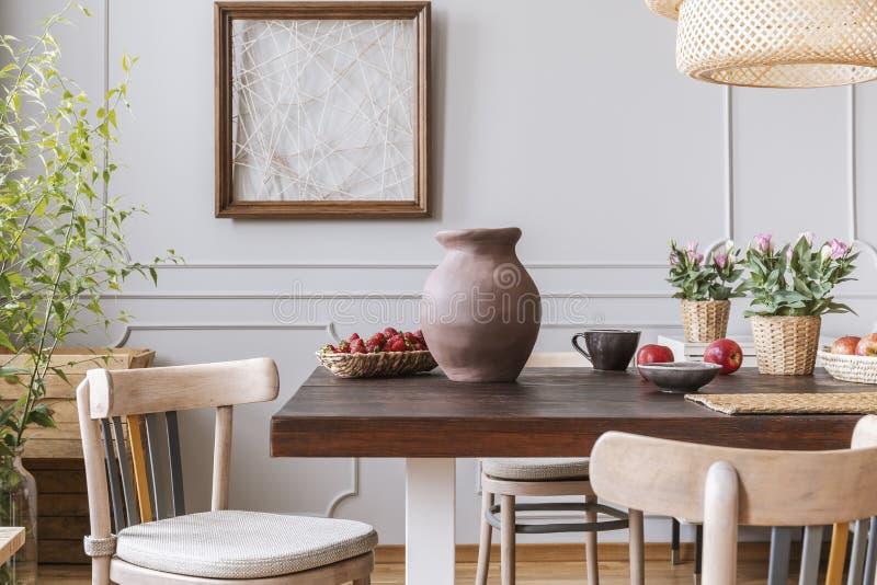 Sillas de madera en la tabla con el florero y las flores en interior gris del comedor con el cartel Foto verdadera fotos de archivo
