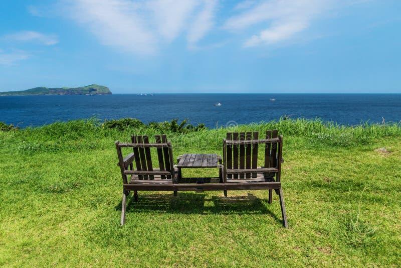 Sillas de madera en prado de la hierba con la opinión sobre el océano y Udo Island, isla de Jeju, Corea del Sur fotografía de archivo