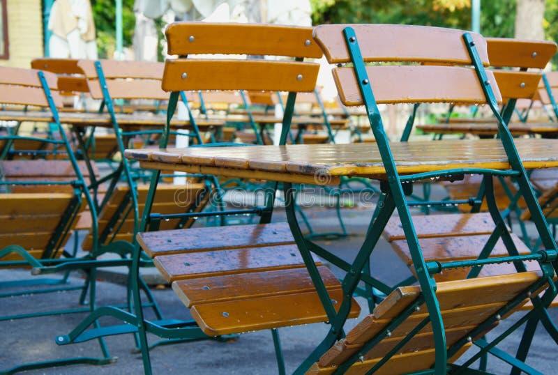 Sillas de madera que se inclinan en las tablas en café o restaurante cerrado durante la mañana después de la lluvia fotografía de archivo