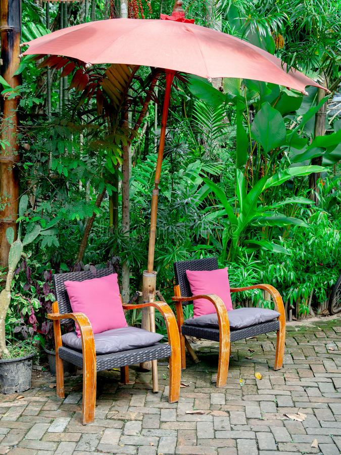 Sillas de madera viejas del vintage con el paraguas rosado del almohada y de bambú en el jardín imágenes de archivo libres de regalías