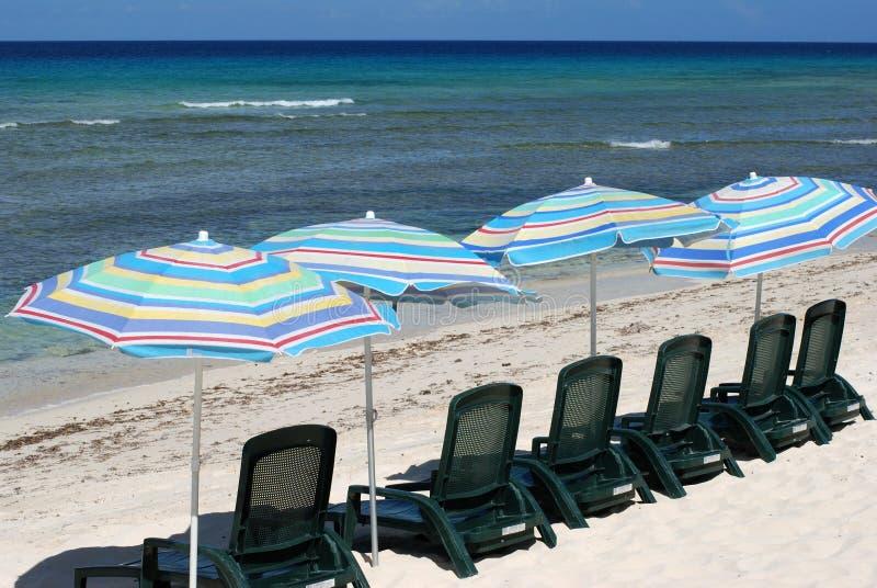 Sillas de playa con los paraguas fotos de archivo libres de regalías