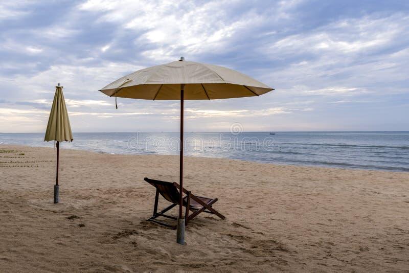Sillas de playa debajo de un paraguas poner crema en la playa fina imágenes de archivo libres de regalías
