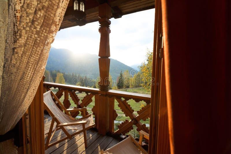 Sillas de una cubierta en el balcón del apartamento del balneario de la montaña Opinión de la ventana en la terraza de madera con imagen de archivo libre de regalías
