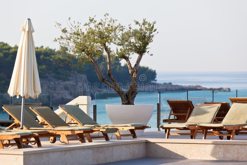 Sillas del Poolside del hotel con la opinión del mar imágenes de archivo libres de regalías