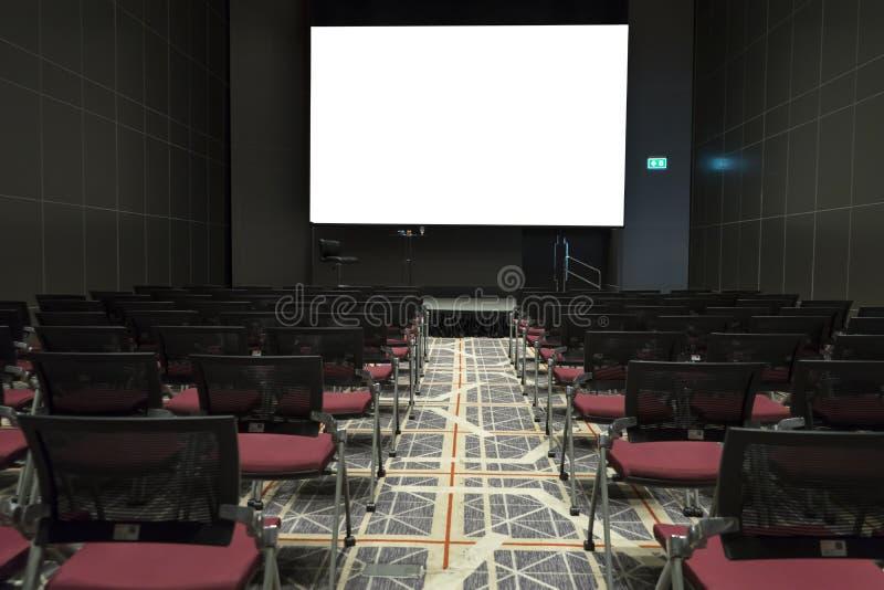 Sillas en etapa de la sala de conferencias magnífica con la pantalla de proyector blanca fotos de archivo libres de regalías
