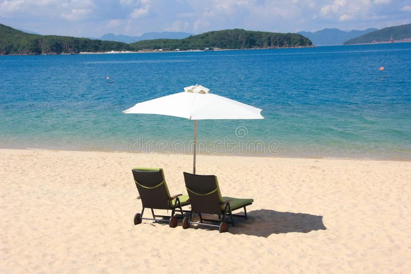 Sillas en la playa arenosa cerca del mar imagen de archivo libre de regalías