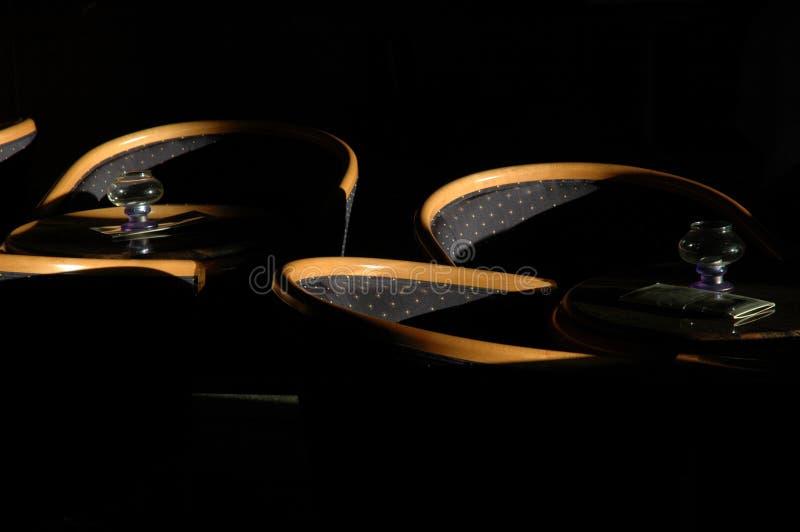 Sillas en una barra con luz del sol del scarse y porciones de sombra fotos de archivo
