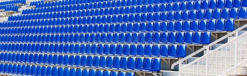 Sillas plásticas azules dobladas en una tribuna temporal fotos de archivo