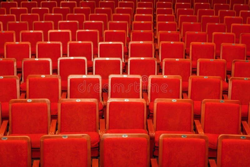 Sillas rojas para la audiencia en el cine o el teatro imagen de archivo libre de regalías