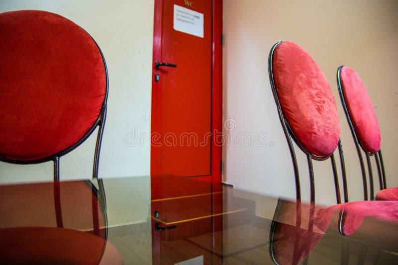 Sillas rojas y puerta roja foto de archivo