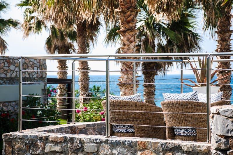 Sillas vacías de la rota en un balcón del ` s del centro turístico que hace frente al mar fotografía de archivo
