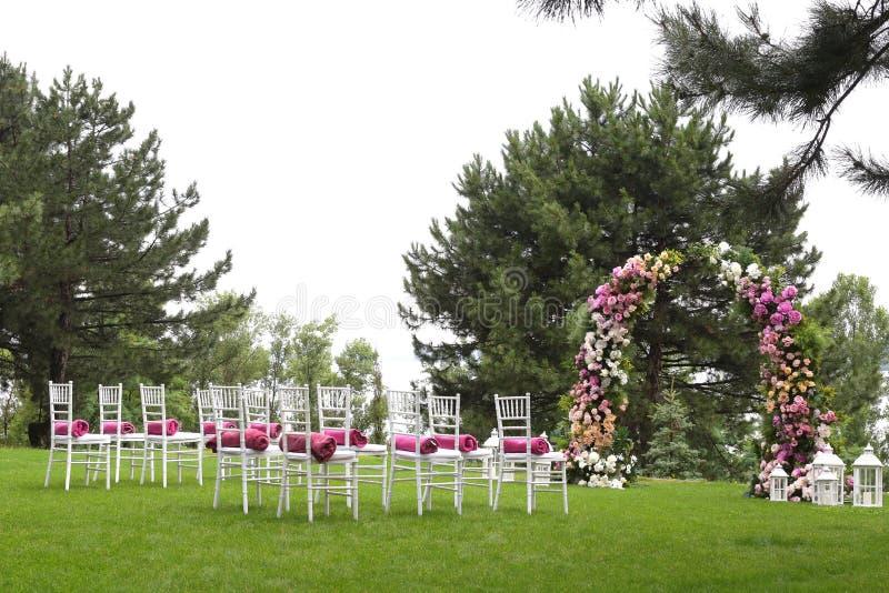 Sillas vacías de madera blancas en fila y arco floral en hierba verde Decoraciones de la ceremonia de boda imagen de archivo