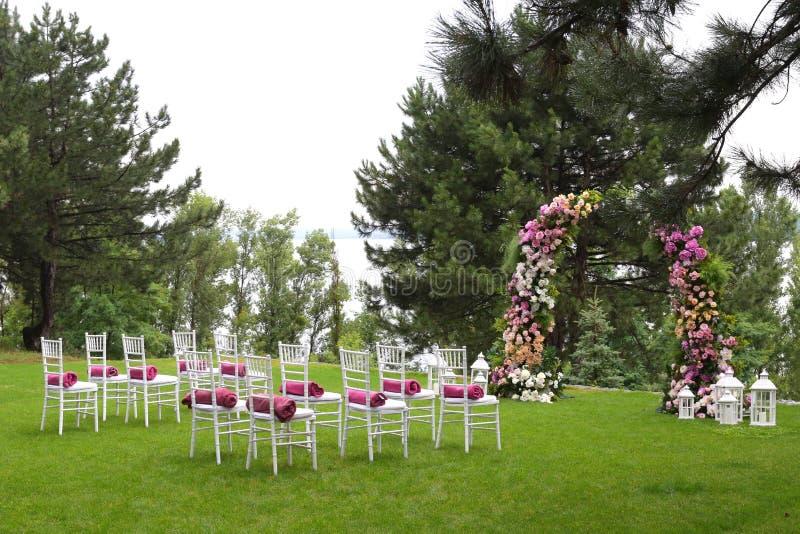 Sillas vacías de madera blancas en fila y arco floral en hierba verde Decoraciones de la ceremonia de boda imagen de archivo libre de regalías