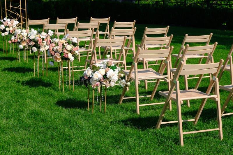 Sillas vacías de madera blancas en fila y ramos de las flores en hierba verde Decoraciones de la ceremonia de boda fotos de archivo