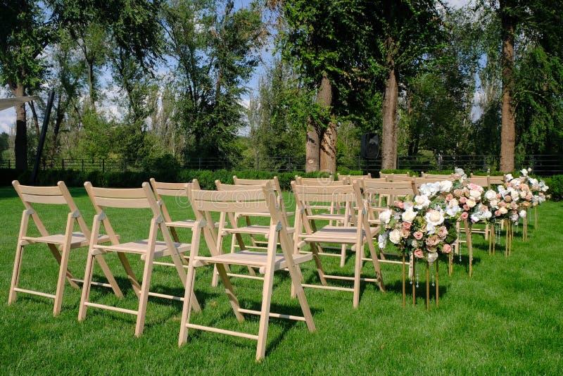 Sillas vacías de madera blancas en fila y ramos de las flores en hierba verde Decoraciones de la ceremonia de boda foto de archivo libre de regalías