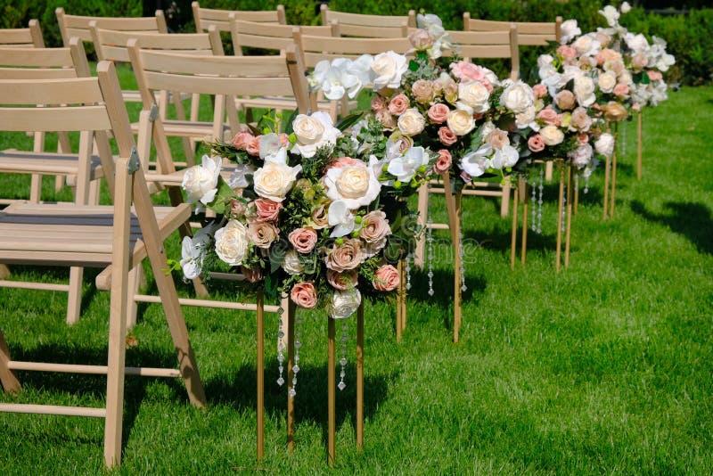 Sillas vacías de madera blancas en fila y ramos de las flores en hierba verde Decoraciones de la ceremonia de boda imagen de archivo