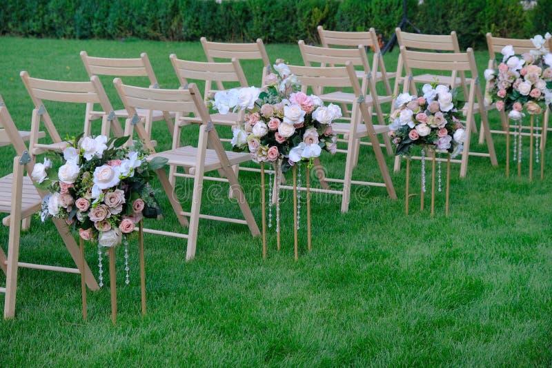 Sillas vacías de madera blancas en fila y ramos de las flores en hierba verde Decoraciones de la ceremonia de boda fotografía de archivo