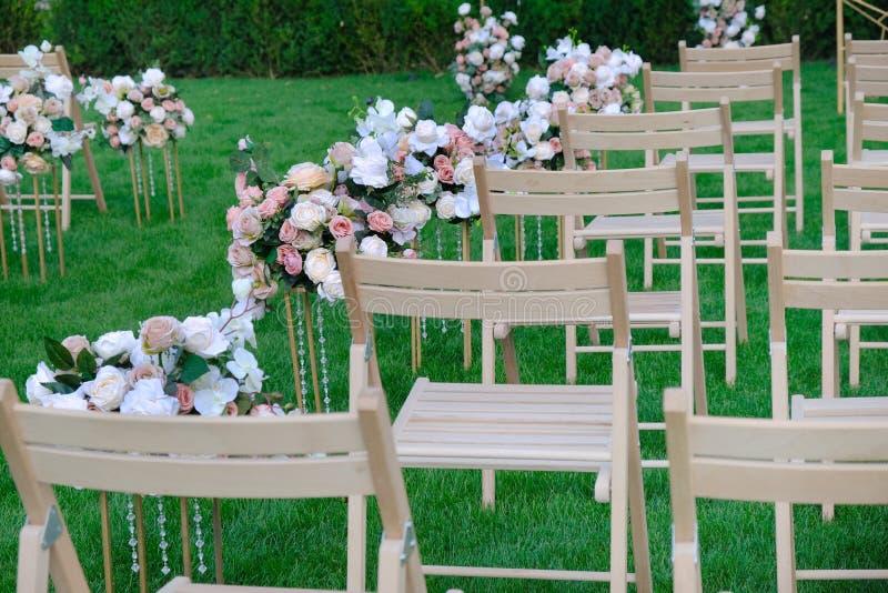 Sillas vacías de madera blancas en fila y ramos de las flores en hierba verde Decoraciones de la ceremonia de boda fotografía de archivo libre de regalías