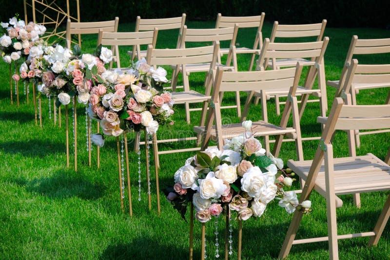 Sillas vacías de madera blancas en fila y ramos de las flores en hierba verde Decoraciones de la ceremonia de boda foto de archivo