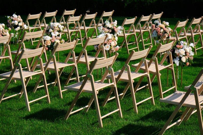 Sillas vacías de madera blancas en fila y ramos de las flores en hierba verde Decoraciones de la ceremonia de boda fotos de archivo libres de regalías